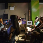 "A picture of the audience who are listening to the artists presenting their works on the open mic nights. In the background there are several painted works on display. EDSA collaborated with TACU and La Cueva de Tarzan to host an ""Open Mic Night"" as part of La Cueva de Tarzan's 9th Anniversary Celebration."