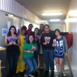 Students in different costumes holding pamphlets for the Open House.
