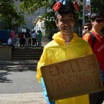 A student in a hazmat suit holding a hand made sign that says English Department as means of promotion for the Open House.