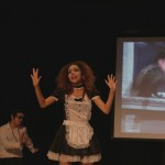 Cast member for the student presented play of The Rocky Horror Picture show on stage holding her hands up.