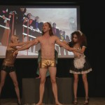 Cast member for the student presented play of The Rocky Horror Picture show on stage with the film being displayed in the background. A male character is standing in the middle with two female characters holding him by each arm.