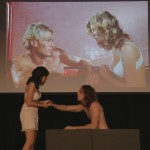 Cast members for the student presented play of The Rocky Horror Picture show on stage are reenacting a scene while the film is displayed in the background.