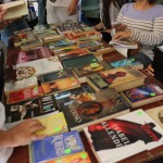 A closer look at all of the books on top of the second table of the EDSA Book & Bake Sale. Some customers are looking at the pages of a book.