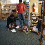 EDSA members helping a child in costume to setup his mask hile sitting on the floor.