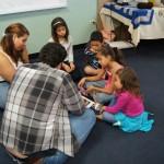 Children sitting in a circle alongside two EDSA members.