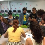 Students gathered around a table partaking in a game, trying to figure out where the books were hidden.