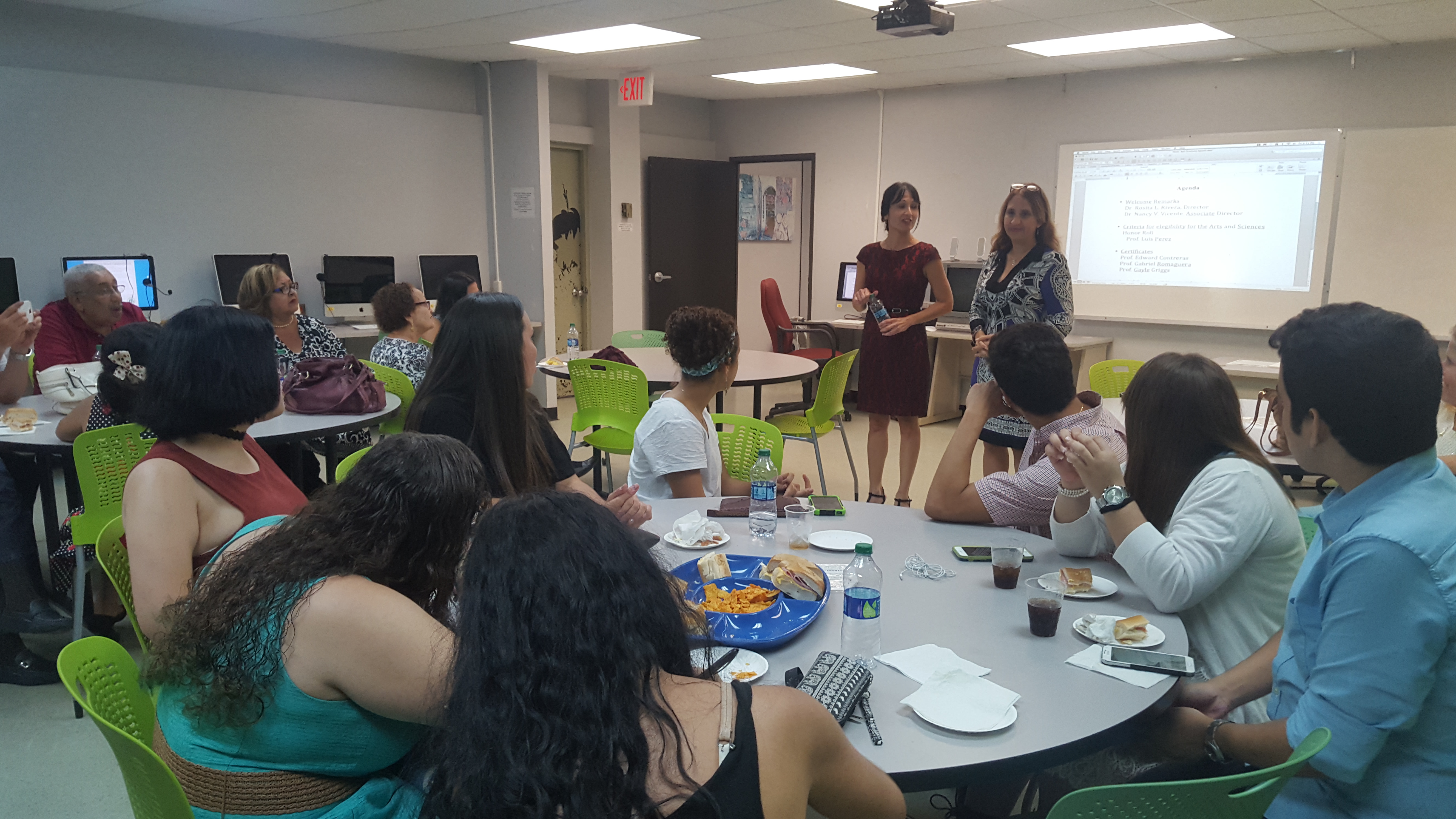 Two college professors speaking in front of a room at the Honor Roll Students Celebration. Students are sitting at the tables and there are snack trays on top of the tables.