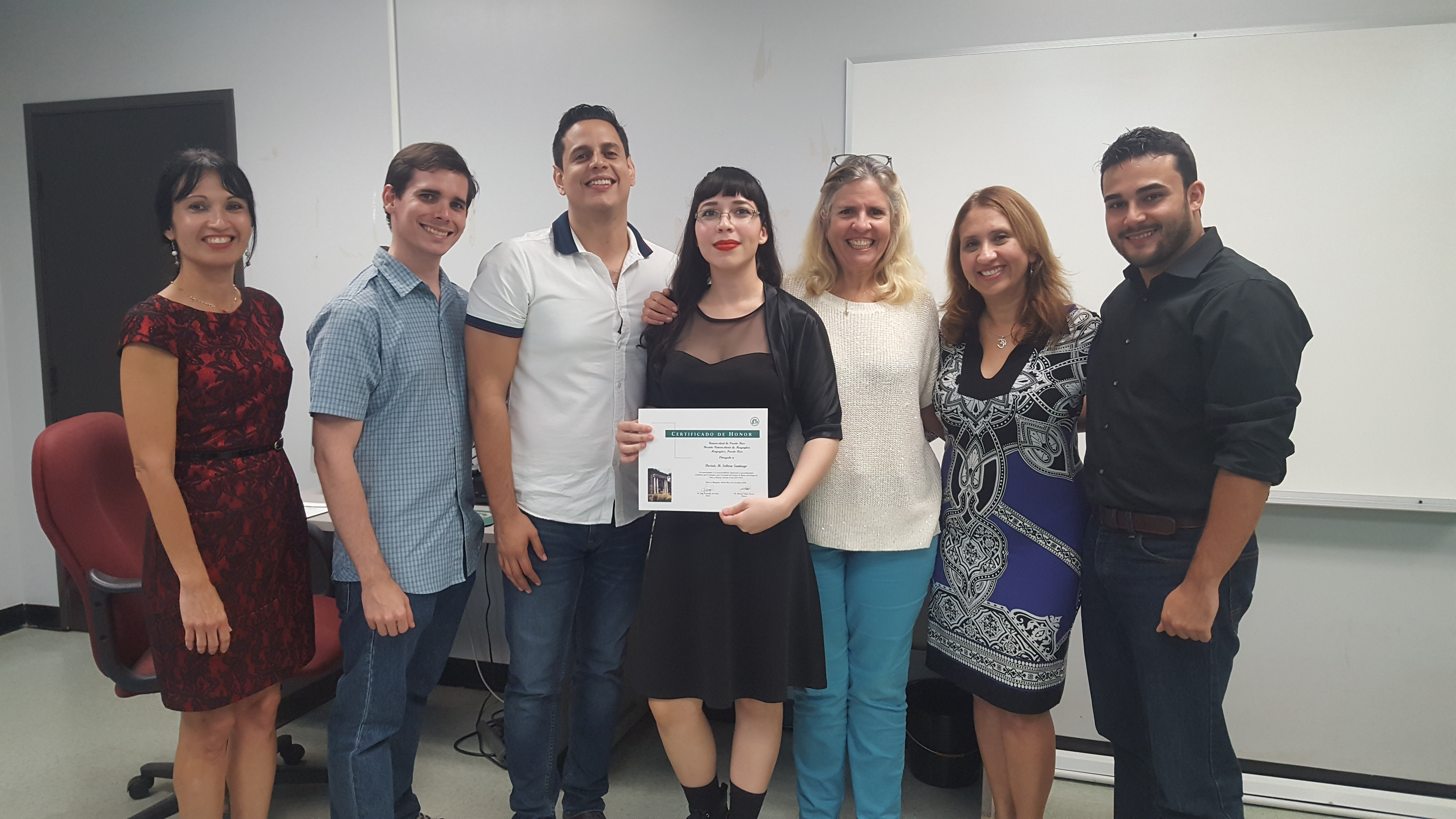 Students and professors posing for the camera at the Honor Roll Students Celebration. The student, at the middle, is holding up the certificate.