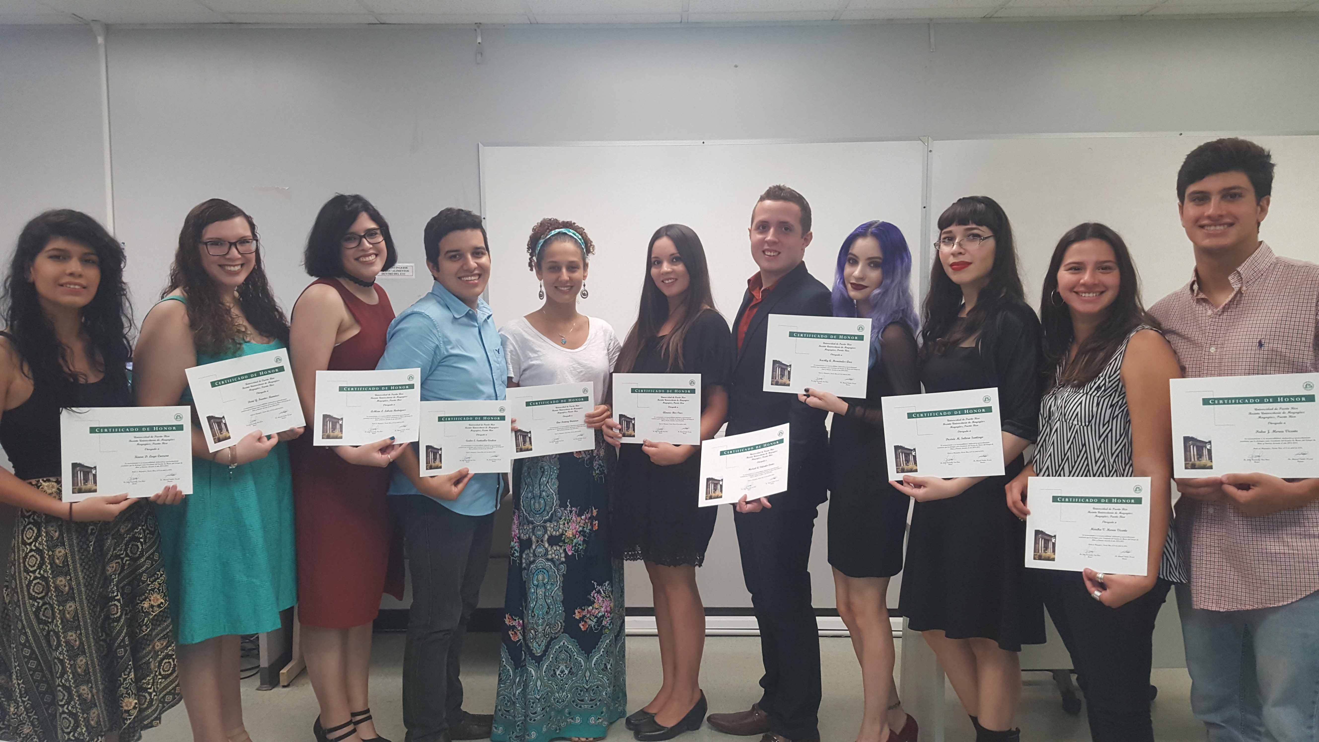The Honor Roll Students posing for the camera while holding up their certificates.