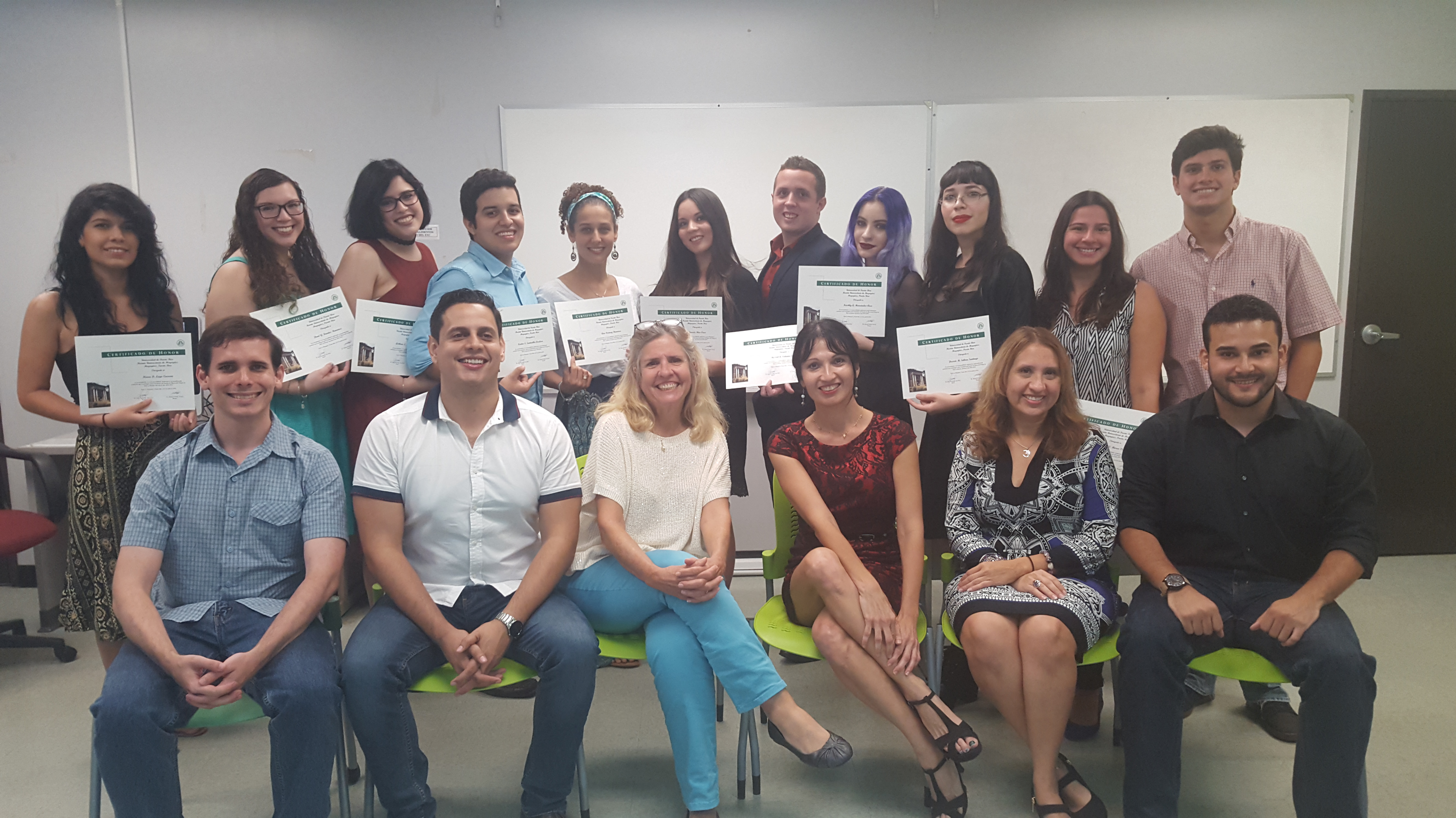 The Honor Roll Students posing for the camera while holding up their certificates (background) and the faculty members posing along with them (foreground).