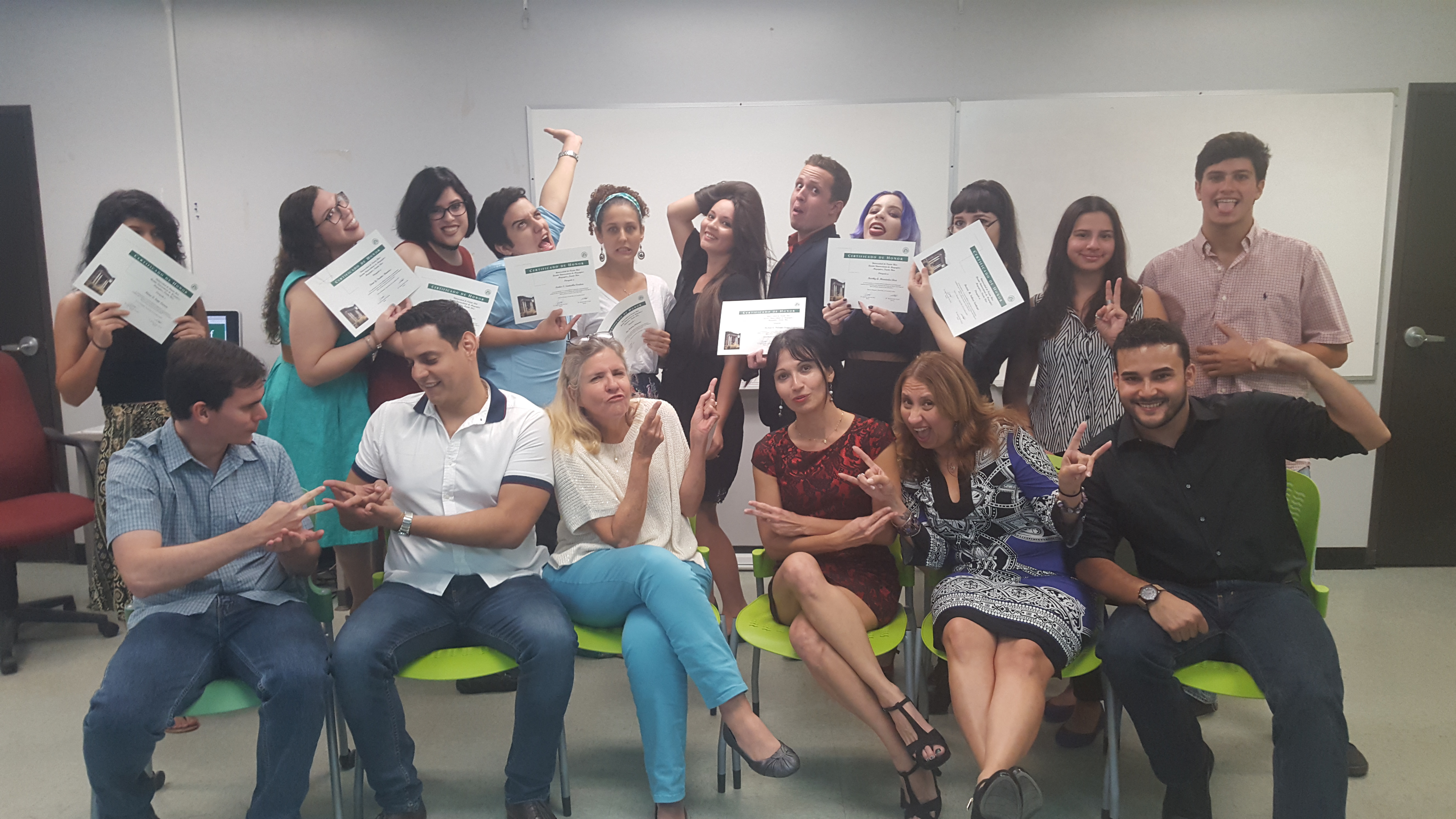 The Honor Roll Students posing for the camera while holding up their certificates (background) and the faculty members posing along with them (foreground). This time trying a funny face on.