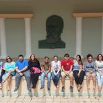 Students sitting in front of a Eugenio Maria de Hostos effigy, posing for the camera.