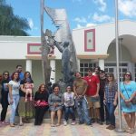 Students sitting in front of a Eugenio Maria de Hostos sculpture, posing for the camera.