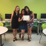 A student is posing for the camera, holding up a certificate, standing in the middle, accompanied by Nancy Vicente (left) and Rosita Rivera (right).