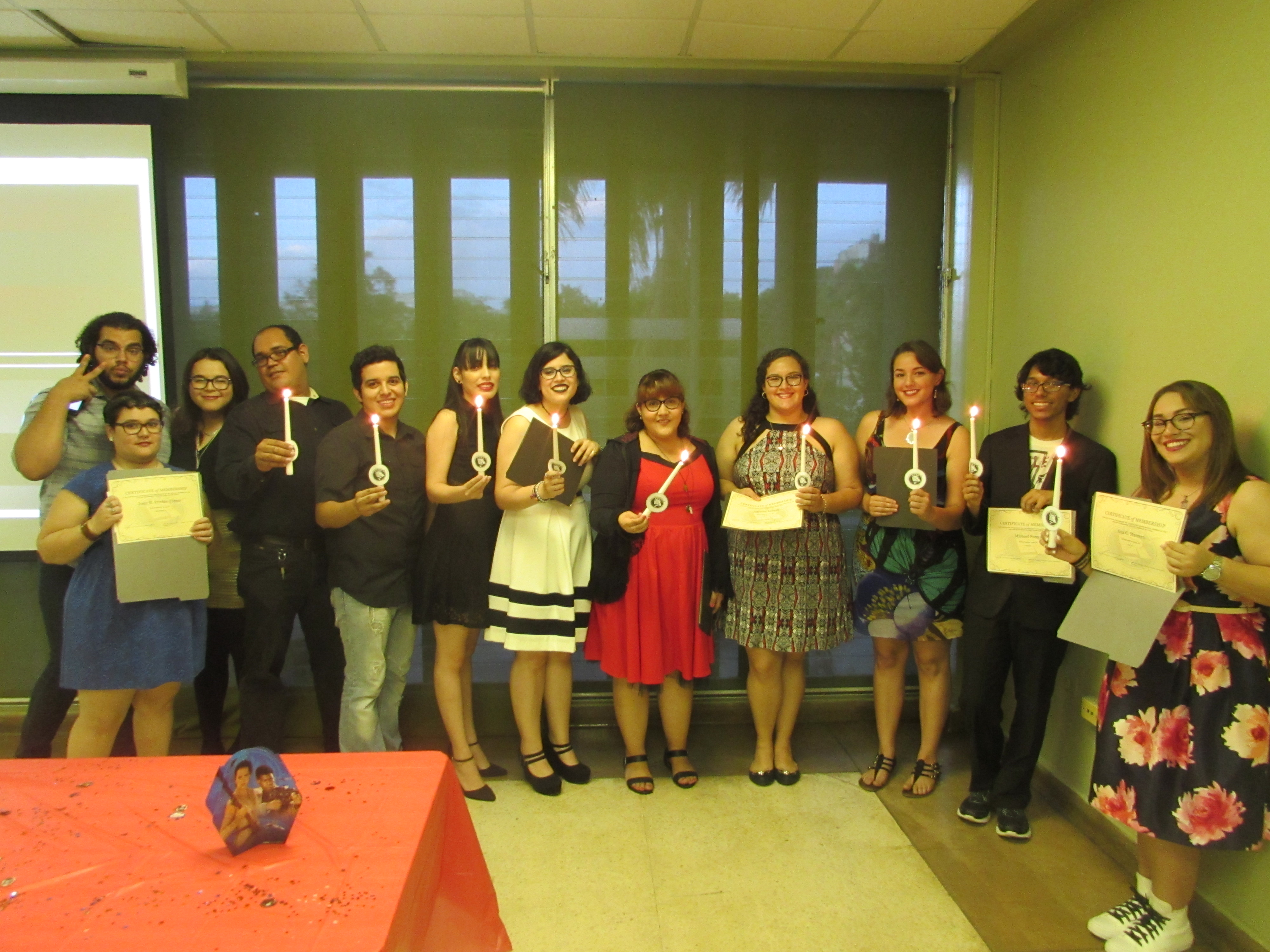 Attendants of the joint activity of May the 4th Be with you by EDSA & PCSA holding up lit candles and certificates, posing for the camera.