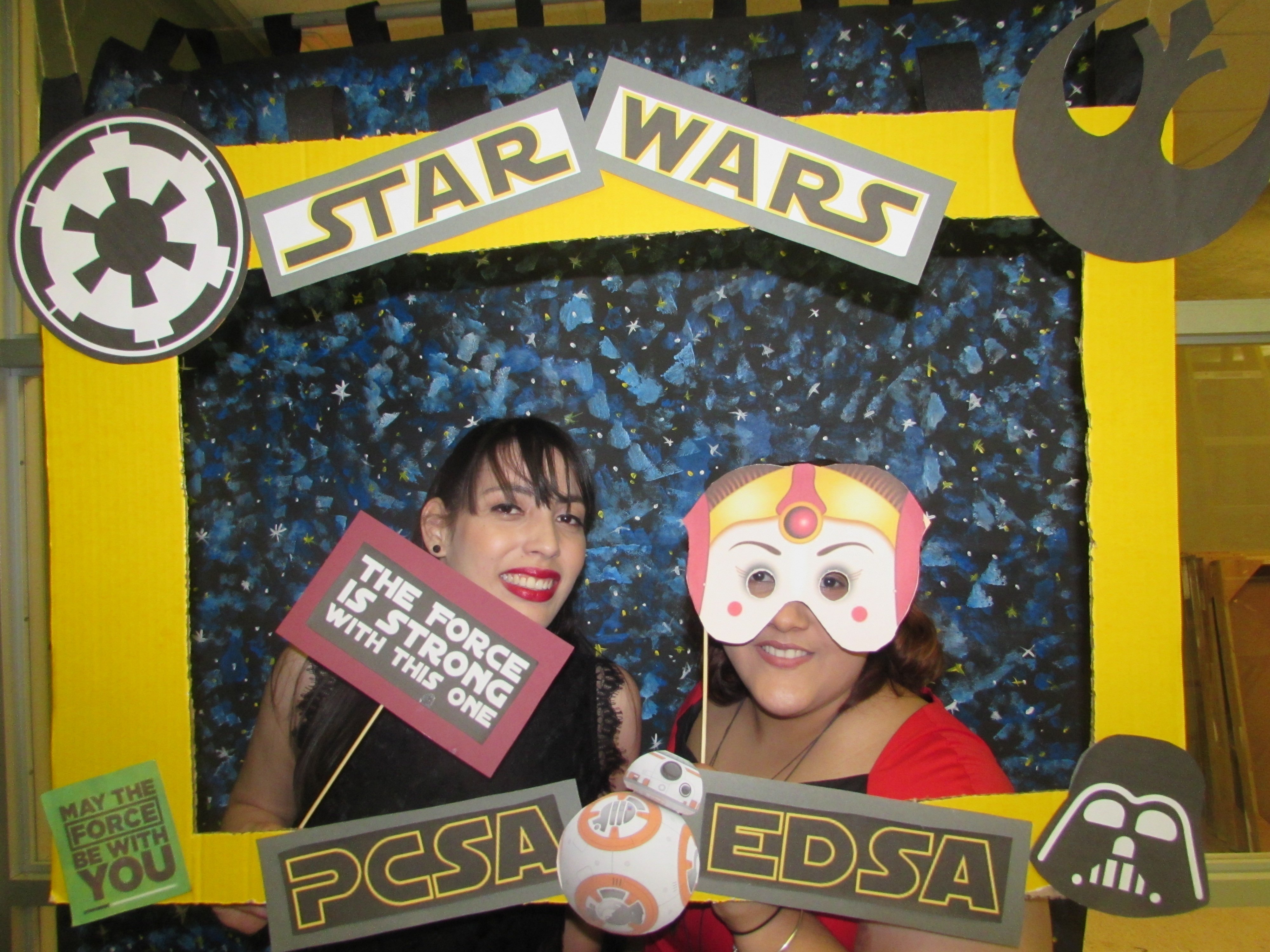 Attendants of the joint activity of May the 4th Be with you by EDSA & PCSA posing for the camera while holding up a promotional frame for PCSA and EDSA and wearing masks.