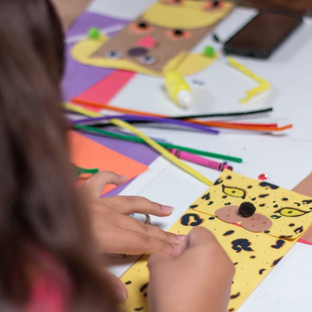 A hand puppet is resting on the table with crayons and other materials for crafts.