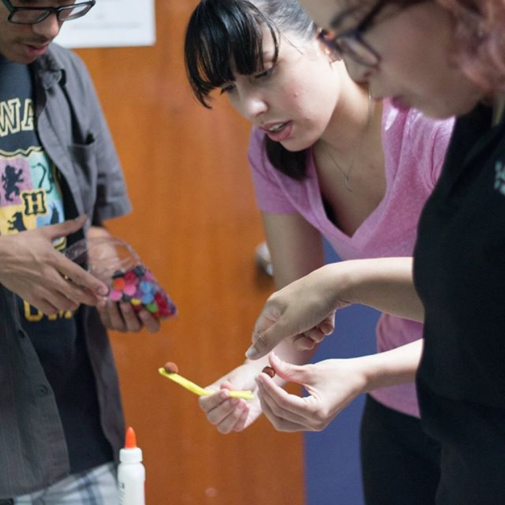 EDSA members helping kids glue some materials together.