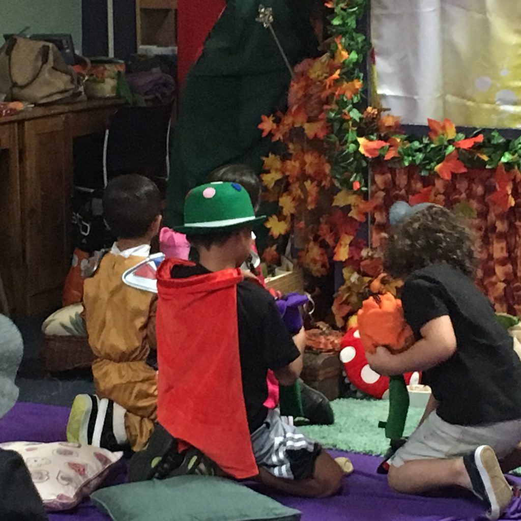 Children are playing close to the puppet stage with different plush towns and other toys found on the floor.