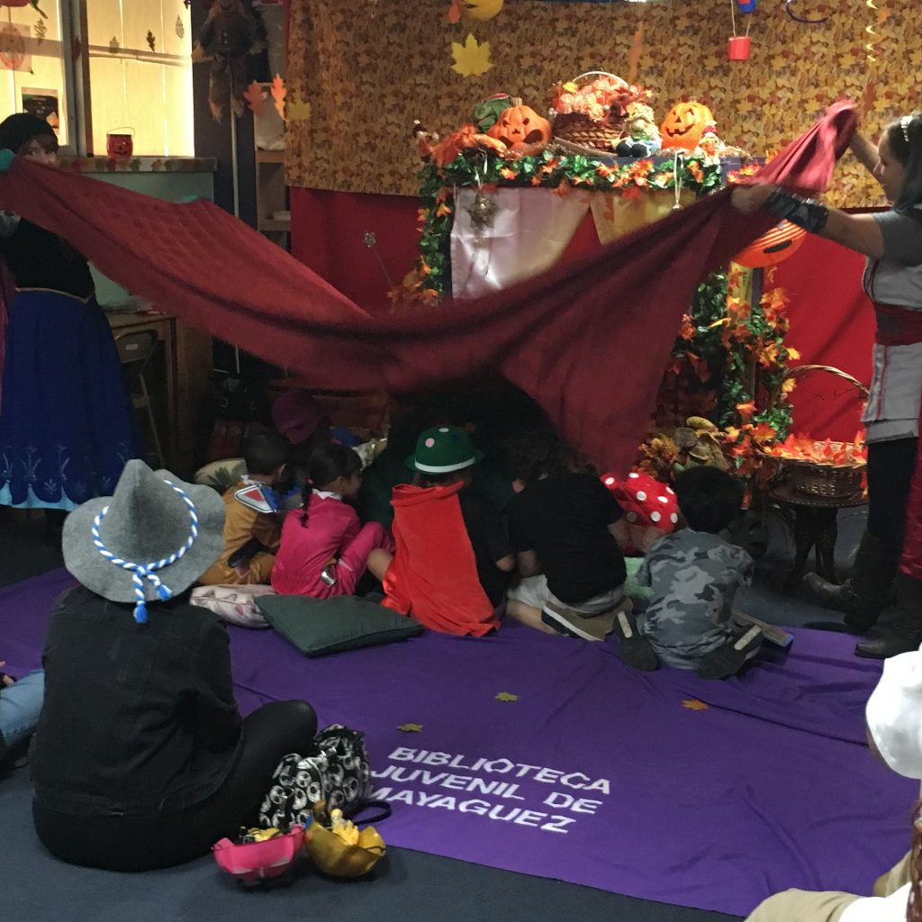 Children are being playfully covered with a blanket at the Children's Library Puppet Show.