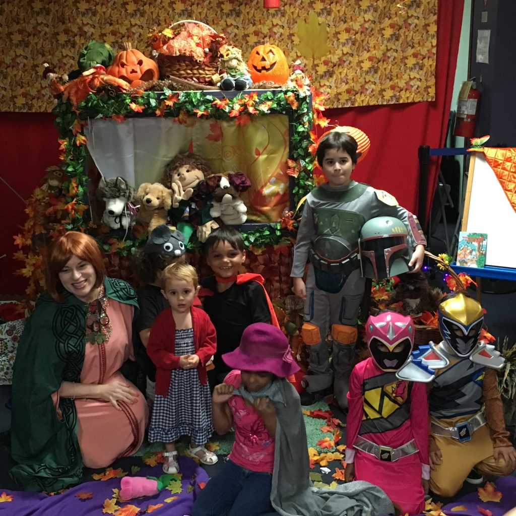 Children are posing for the camera in costume next to the Halloween Theme decorated puppet stage.