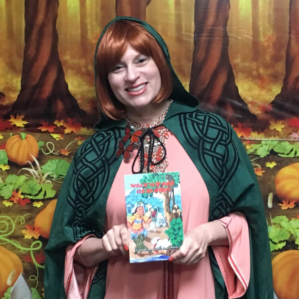 A woman is holding up a copy of a book while in costume portraying the main character of the book.