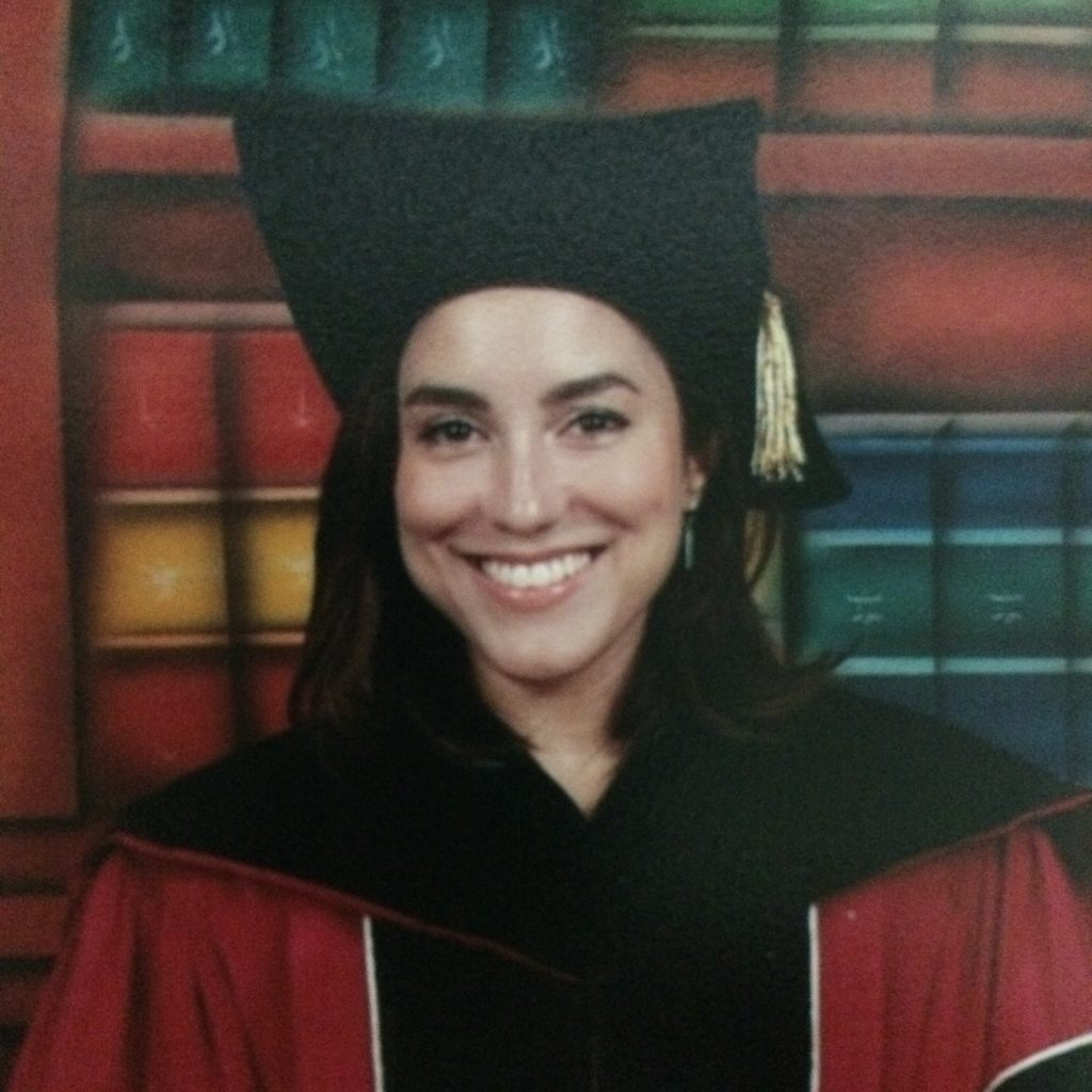 María Quintero Aguiló in her graduation robe smiling for the camera.