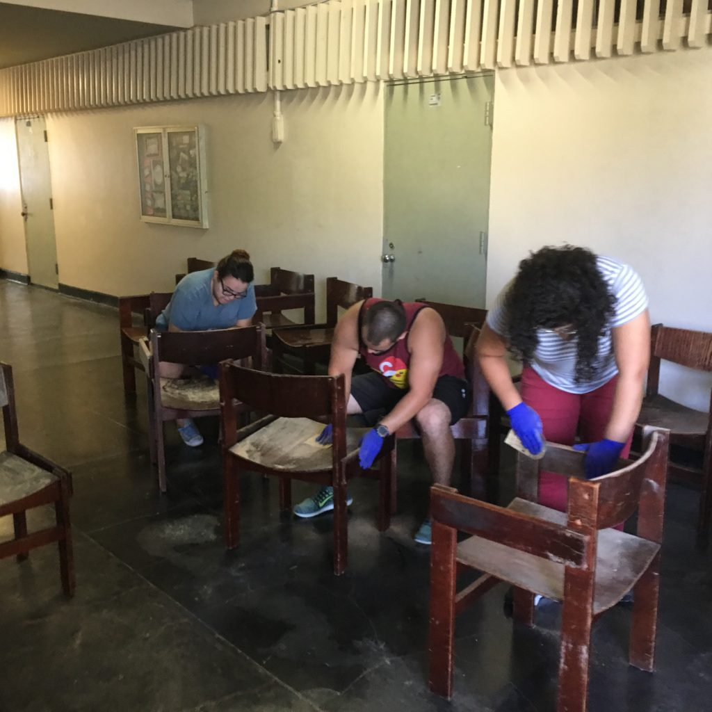 English Department's students cleaning chairs in the hall.