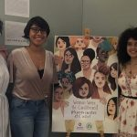 Two English department's students holding a poster for the exhibit Women write the Caribbean, made by Carol Rosetti.