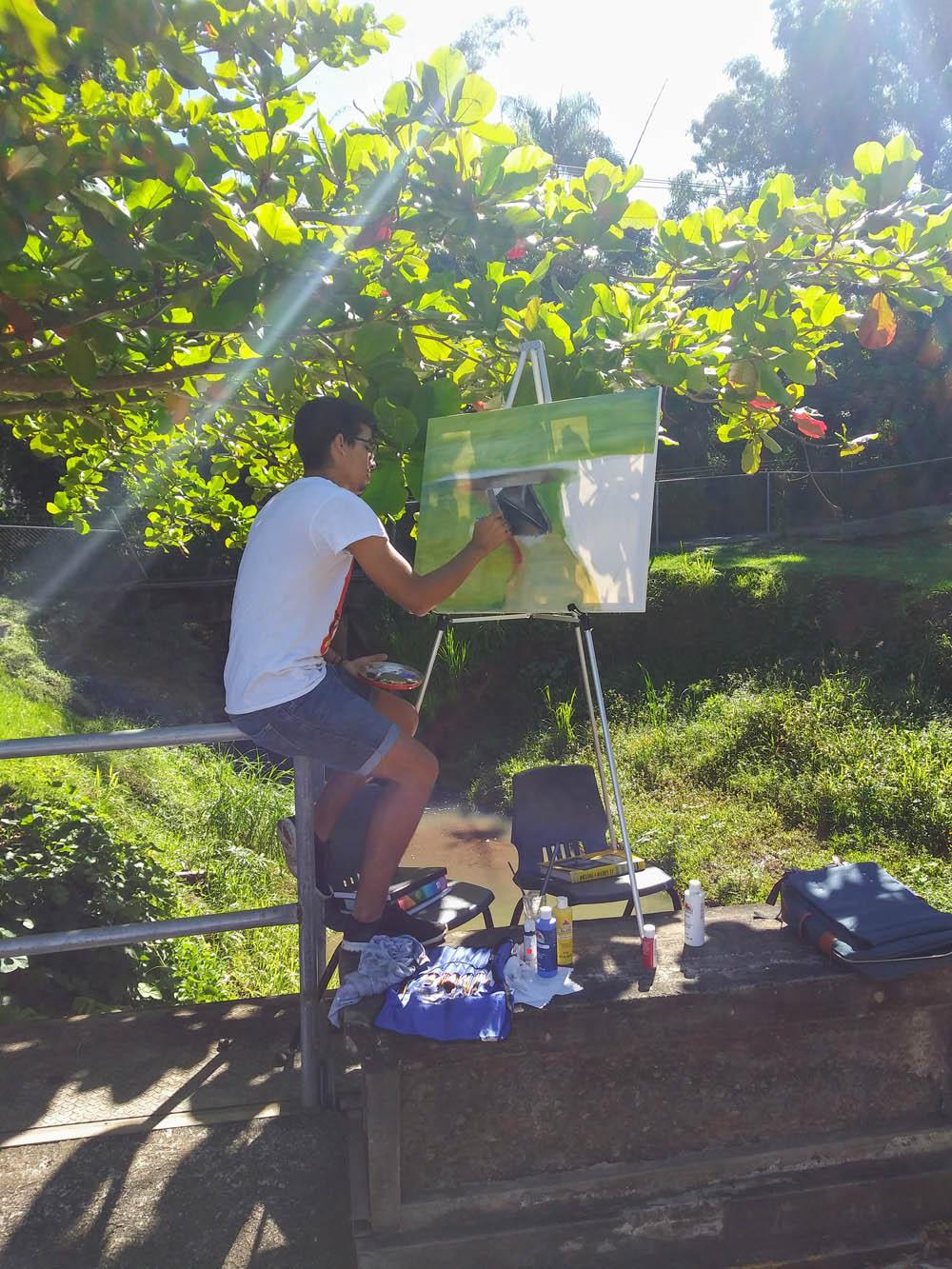 Estudiante pintando frente a Taller de Artes