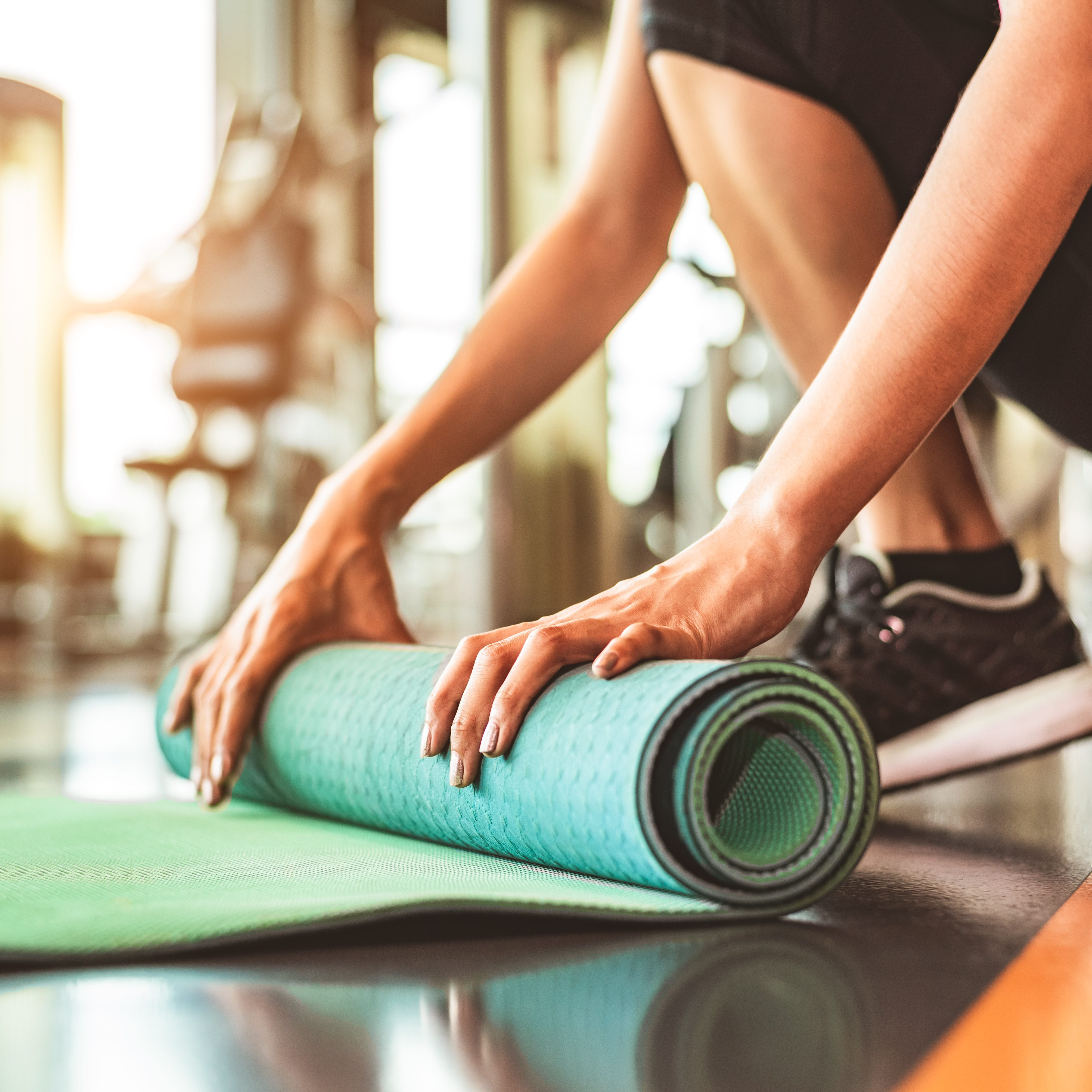 Close up of sporty woman folding yoga mattress in sport fitness gym training center background. Exercise mat rolling keeping after yoga class. Workout and sport training concept. Hands on carpet