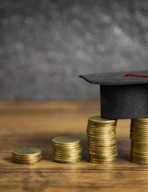 Scholarships education concept with graduation cap on coin money saving  for grants education on wooden table dark background